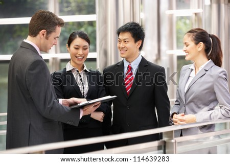 Four Business Colleagues Discussing Document Outside Office - stock photo