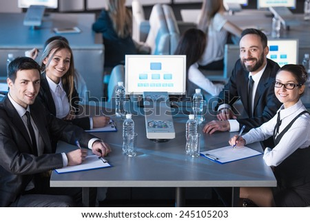 Four business people are sitting at the table in a modern conference hall during the presentation and looking at the camera. - stock photo
