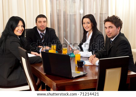 Four business people in black suits having a business meeting in a modern workplace and sitting on chairs at table with juices,coffees and papers - stock photo