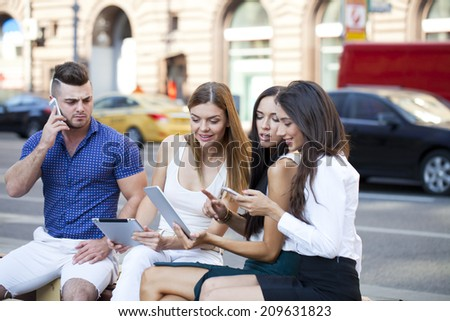 Four business people sitting on a bench in the summer city - stock photo