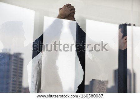 Four business people standing and cheering with hands together on the other side of glass wall - stock photo