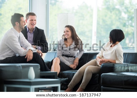 Four business people talking on a break in modern environment - stock photo