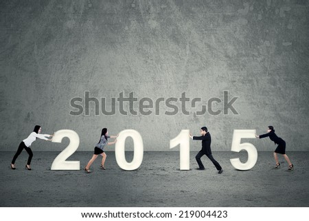 Four business people working together to arrange number of 2015 - stock photo