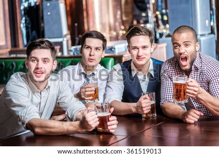 Four businessmen drink beer and rejoice and shout together watching TV at the bar. Successful businessmen friends having fun together in the bar with a beer watching football on TV - stock photo