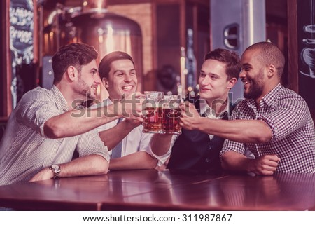 Four businessmen drink beer and rejoice together at the bar. Confident business people having fun with friends at the bar with a beer. - stock photo
