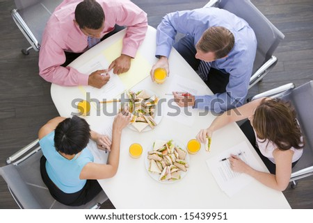 Four businesspeople at boardroom table with sandwiches - stock photo