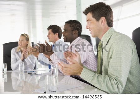 Four businesspeople in a boardroom applauding - stock photo