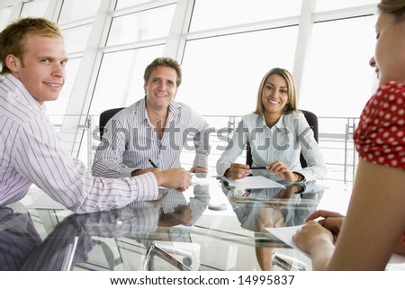 Four businesspeople in a boardroom with paperwork smiling - stock photo