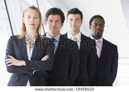 Four businesspeople standing in corridor - stock photo