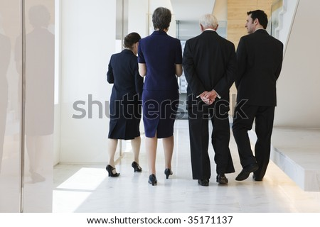 Four businesspeople walking - stock photo