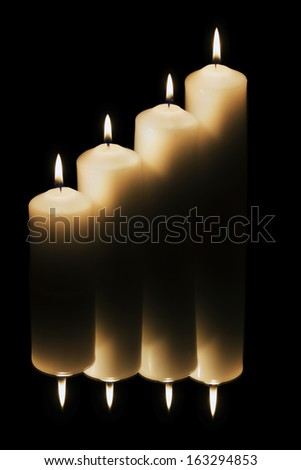 Four candles reflected with dark background - stock photo