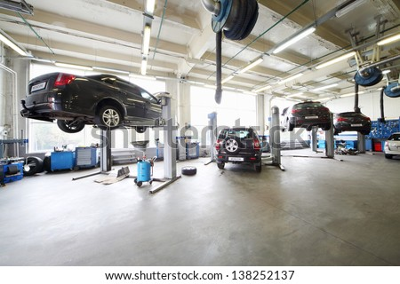 Four cars on lifts and on floor in small service station. Cars prepared to diagnosis and repair. - stock photo