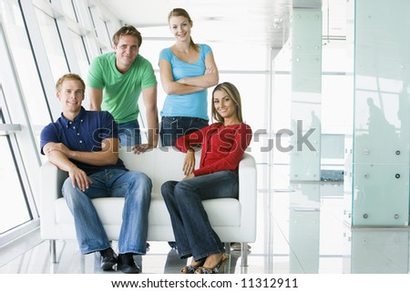Four casually dressed business people in office - stock photo