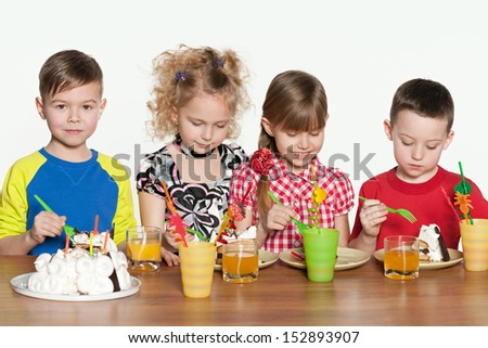 Four cheerful children celebrate a birthday at the table - stock photo