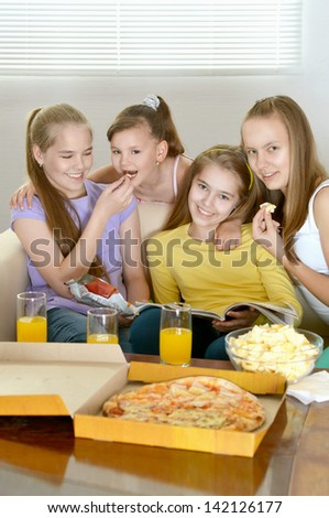 Four cheerful girls relaxing at home together - stock photo