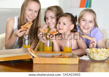 four cheerful girls watching TV together - stock photo