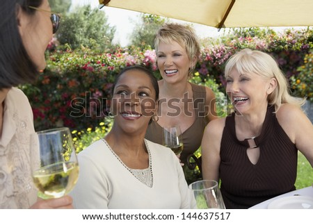 Four cheerful multiethnic middle aged women chatting with wine glasses at the garden party - stock photo