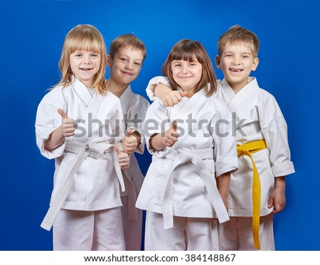 Four cheerful sportsman in karate gi are showing finger super - stock photo
