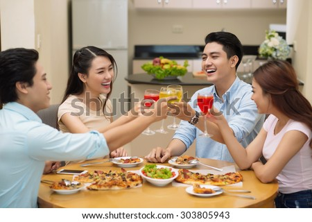 Four cheerful young friends clinking glasses at the dinner - stock photo