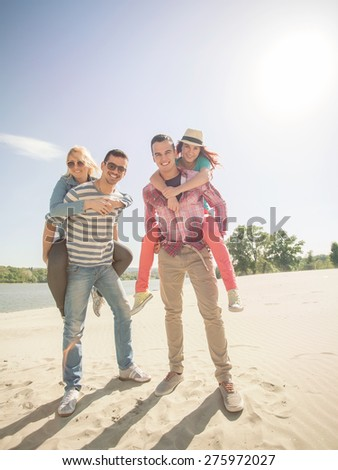 Four cheerful young friends enjoying summertime on the beach - stock photo