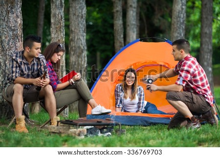 Four cheerful young friends relaxing after barbecue while camping in nature - stock photo