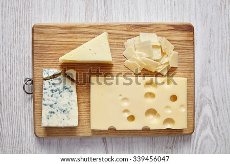 four cheeses on white wooden table and chopping board - stock photo