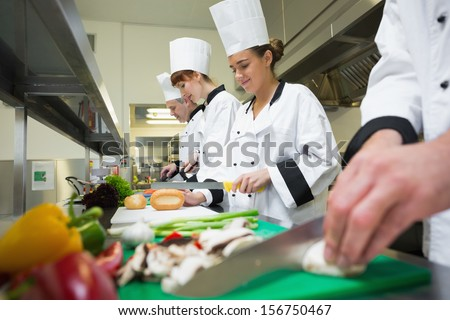 Four chefs preparing food at counter in a row in a professional kitchen - stock photo