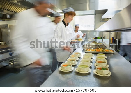Four chefs working in a modern kitchen preparing soups - stock photo