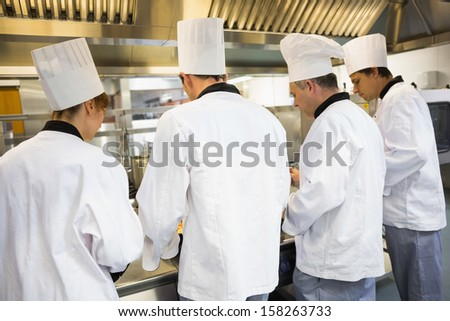 Four chefs working in industrial kitchen while wearing uniforms rear view - stock photo
