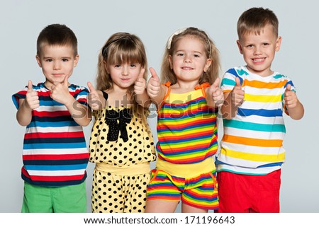 Four children are standing together on the grey background - stock photo