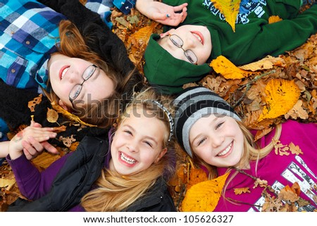 four children lying down on autumn leaves birds eye view - stock photo
