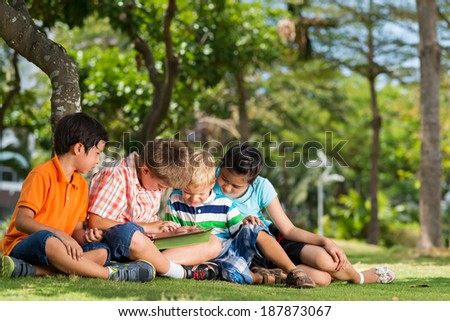 Four children playing with a digital tablet in the park - stock photo