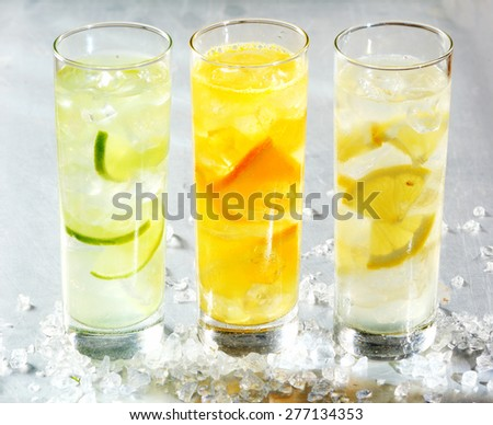 Four chilled citrus beverages with sliced lemon, orange and lime in white spirits for a refreshing summer cocktail served in long glasses - stock photo
