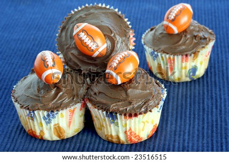 Four chocolate cupcakes with football decorations perfect for football or Father's Day treats - stock photo