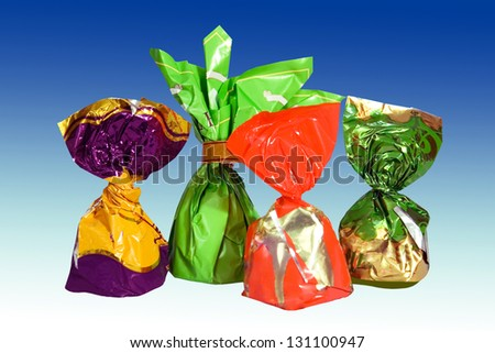 four chocolates in a colored shiny packaging. white background. - stock photo