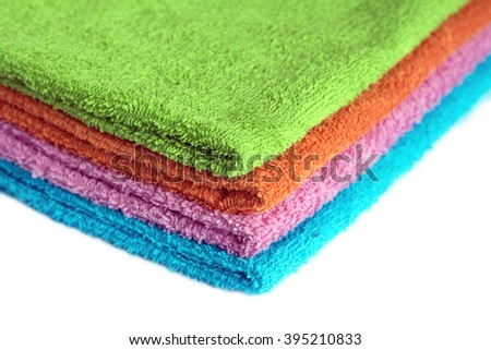 Four clean soft double bath towels set of different colors stacked isolated on white background. Side view from corner close-up - stock photo