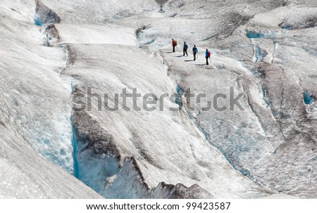four climbers on ice of norwegian glacier - stock photo