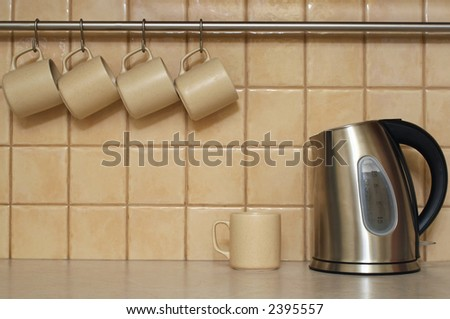 Four coffee cups hanging in a row. Single cup and electric cordless kettle sitting on table - stock photo