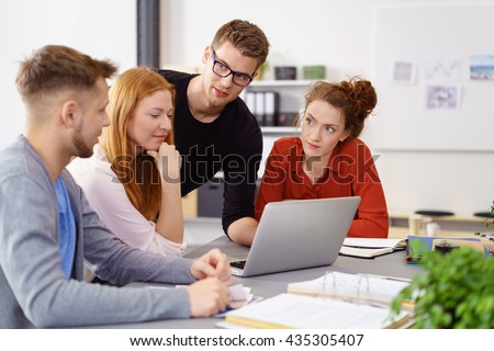 Four colleagues conducting business meeting using laptop computer in large office on sunny day - stock photo