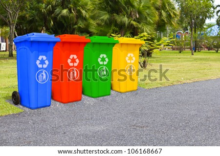 Four color trash cans (garbage bin) in the park beside the walk way - stock photo