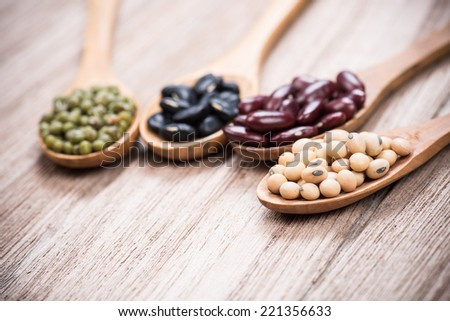 four colored beans in wooden spoon.selective focus is soybeans - stock photo