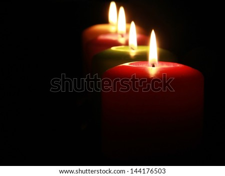 four colored lighting candles on dark background, selective focus - stock photo