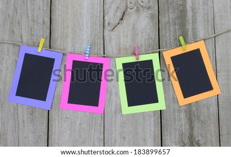 Four colorful blank cards hanging on clothesline with wooden background - stock photo