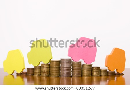 Four colorful car shapes over stacked coins - stock photo