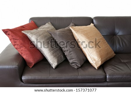 Four colorful cushions on dark brown leather couch - stock photo