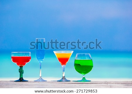 Four colorful exotic tasty cocktails background turquoise sea - stock photo