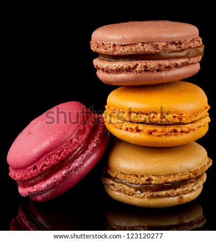 Four colorful macarons isolated on black background - stock photo