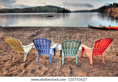 Four colorful patio chairs overlooking a lake with Canoes along the shore. - stock photo