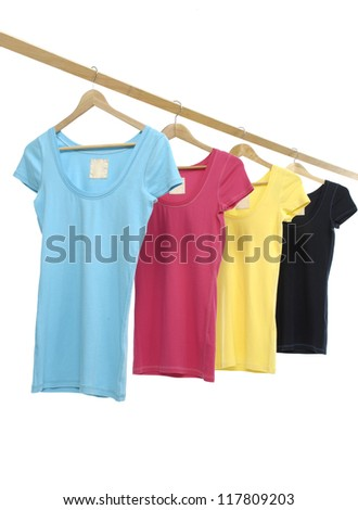 Four colorful shirts on wooden hangers - stock photo