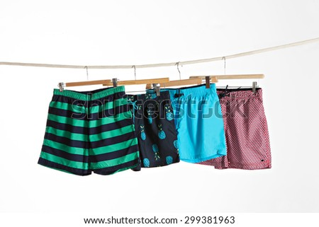 four colorful swimwear in a rope on a white background - stock photo